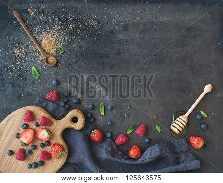 Berry frame with copy space on right. Strawberries, raspberries, blueberries and mint leaves, honey, cane sugar, dark grunge background, top view, copy space, horizontal