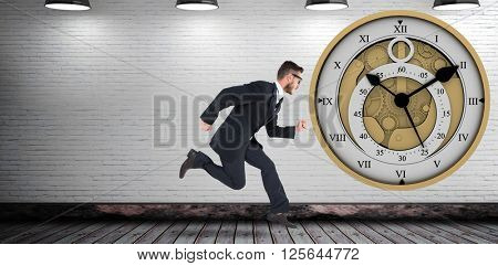 Geeky young businessman running mid air on a grey room and in front of a clock