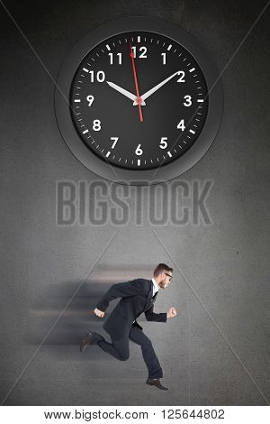 Geeky young businessman running mid air on a black background with a clock