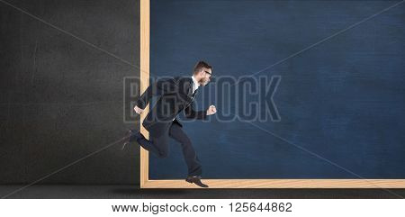 Geeky young businessman running mid air in front of a chalkboard