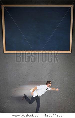 Geeky young businessman running late on grey background with a black board