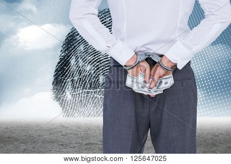 Businessman in handcuffs holding bribe against thumbprint graphic over desert