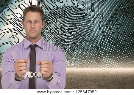 Handsome businessman wearing handcuffs against fingerprint with circuit board graphic