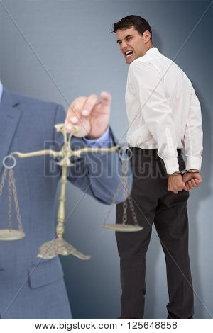 Male lawyer holding scale and gavel against white background against digital image of gray wall