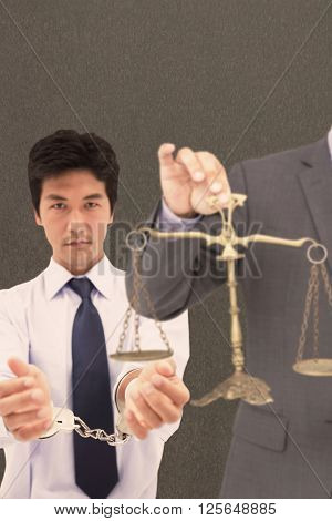 Male lawyer holding scale and gavel against white background against grey background
