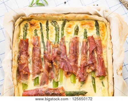 Savory pie with asparagus, prosciutto, marjoram and egg and cream mixture in a baking tin with parchment on checkered table cloth