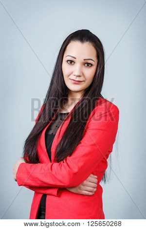 Young  beautiful woman with crossed hands on the gray background