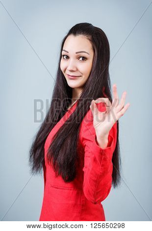 Young beautiful woman shows OK sign on the gray background