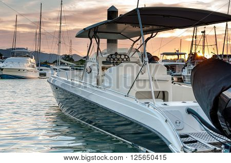 Small motorboat docking at the marina with sunset in Phuket Thailand