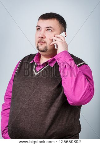 Businessman with overweight speaks on the phone on the gray background