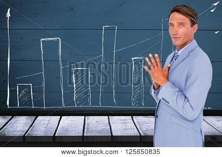 Portrait of confident businessman with hands clasped against a red wall