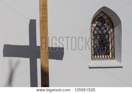 Wooden cross with a years of Saint Missions and its shadow on the wall of the gothic church in Svaty Jur Slovakia. Traditional gothic window beside.