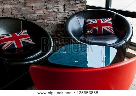 Black chairs with Union Jack pillows with bricks wall behind
