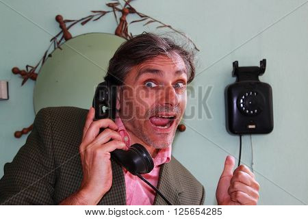 smiling man answering an old fashioned telephone
