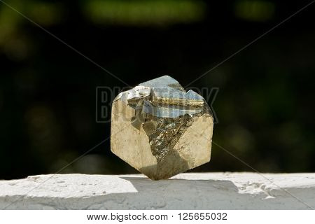 Pyrite cube on white wall and dark background