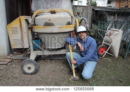 a Construction Worker posing with Mixing Cement