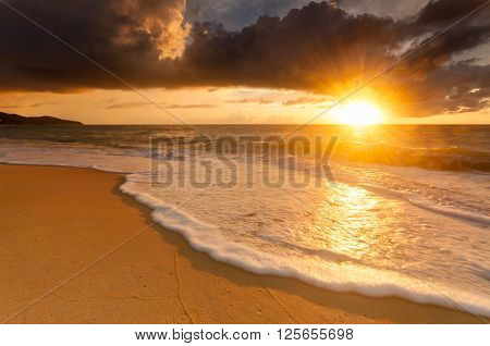 Wave foam bubbles hit the beach at the golden hour after the rain in Phuket Thailand