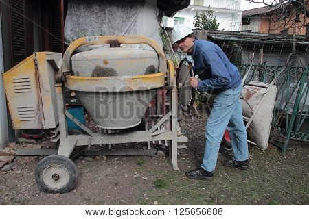 a Construction Worker with Mixing Cement machine