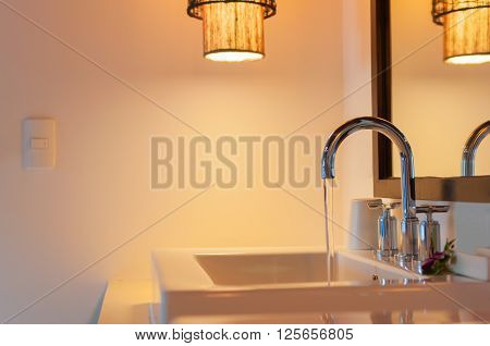Open faucets with water flowing in the bathroom with lamp