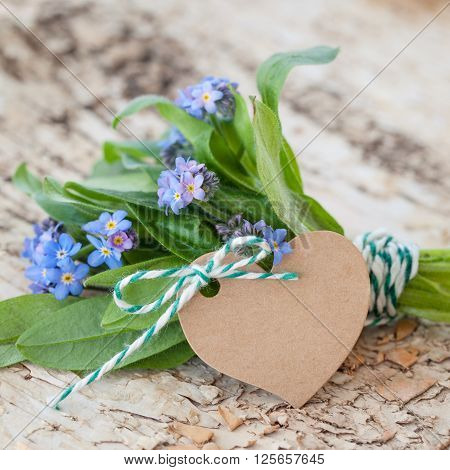 Little bouquet of forget-me-nots on rustic birch wood