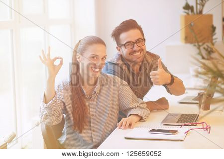 Happy freelance man and woman posing for photographer in office interior while sittin in office interior and showing thumb-up and okay signs.
