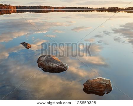 Landscape with three rocks in the water of a lake in Finland. Peaceful view with sky and cloud reflection in the clean and still water.