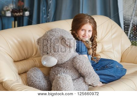 Little cute girl sitting with teddy bear. Stock photo.