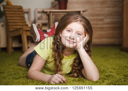 Little girl lie on the grass. Stock photo