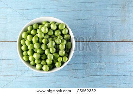 Green peas in wooden bowl on wooden background