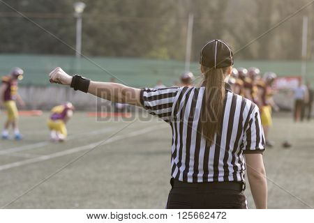 Female football judge in stripped black and white shirts on the field. Players in the background.