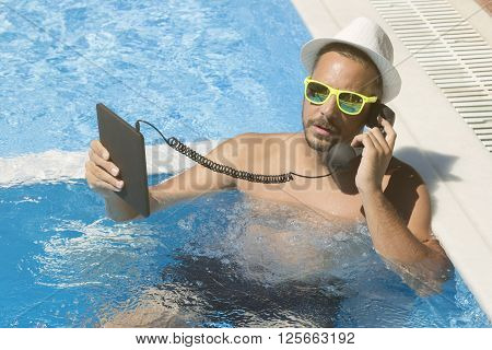 Young man having an internet call in a swimming pool. He is using digital tablet device and retro styled handset.