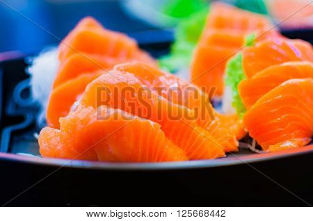 Selective focus of raw fresh sashimi serve in a boat bowl with green wasabi and sliced radish