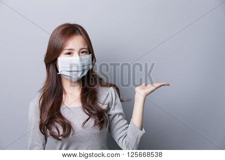 A Woman wears a mask and show something illness asian beautygray background