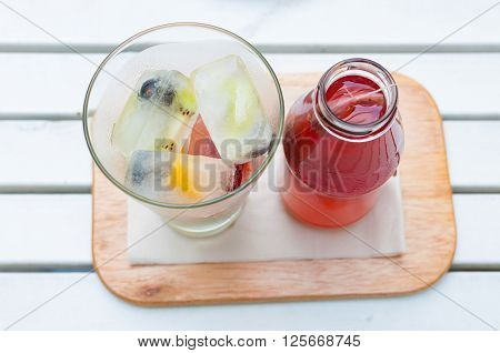Self pouring ice tea serve with ice cube with fruits frozen inside.