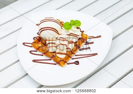 Vanilla ice cream waffle banana with chocolate sauce and mint leaf decorate on top serve on white plates over the white wooden table