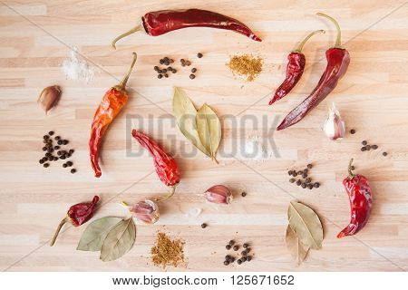 Chili Pepper, Bay Leaf, Black Pepper, Garlic, Salt, Spices On Light Wooden Background With Copyspace