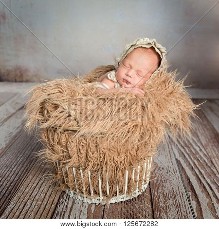 sleepy infant in basket with blanket like weat and hat on wooden floor