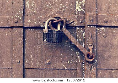 Industrial background - steel black padlock keeping the old door heck at the iron rusty riveted door. Vintage filter applied