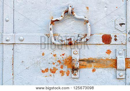 Grunge grey metal door with rusty details - rivets door handle and empty lanch. Metal obsolete background.