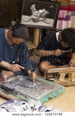 CHIANG MAI, THAILAND - APRIL 13: The artisan carving pewter silver sculpture at the ancient lanna house 140 years in water festival in Chiang Mai Thailand on April 13 2016.
