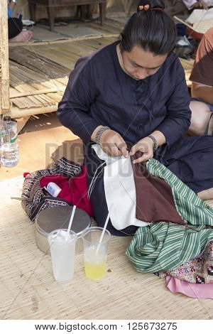 CHIANG MAI, THAILAND - APRIL 13: The woman sewing traditional Thai fabric textile at the ancient lanna house 140 years in water festival in Chiang Mai Thailand on April 13 2016.