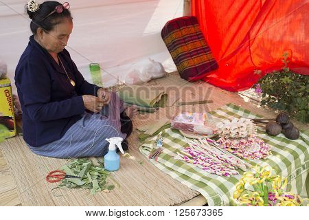 CHIANG MAI, THAILAND - APRIL 13: old woman folding banana leaf at the ancient lanna house 140 years in water festival in Chiang Mai Thailand on April 13 2016.