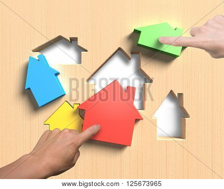 Different colorful houses suit house shape holes of wooden board with woman and man hands pushing to assemble.