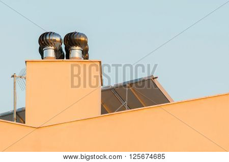 Chimney ventilator fan system on top of a house.