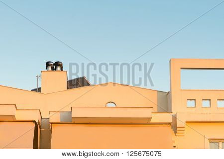Top of a house with a chimney ventilator fan system.