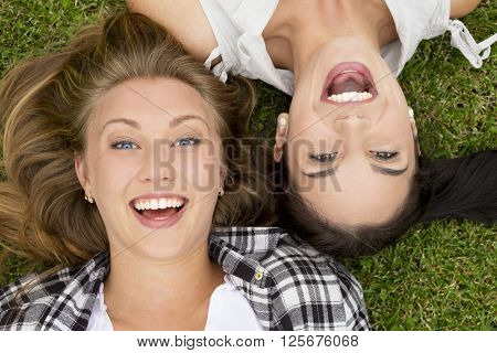 Female best friends lying on the grass and laughing