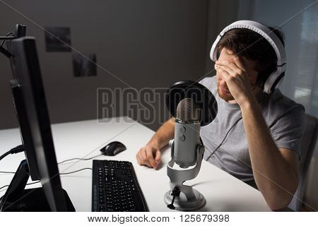 technology, gaming, entertainment, let's play and people concept - close up of sad young man in headset with pc computer playing game at home and streaming playthrough or walkthrough video