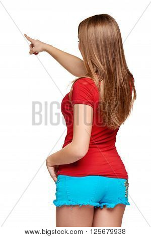 Back view of a young bright female pointing at blank copy space, over white background