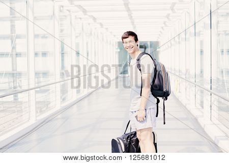 Young hispanic man wearing glasses, t-shirt, shorts and backpack, standing in airport corridor, holding mobile phone and sport handbag in his hands, looking at camera and smiling - travel concept