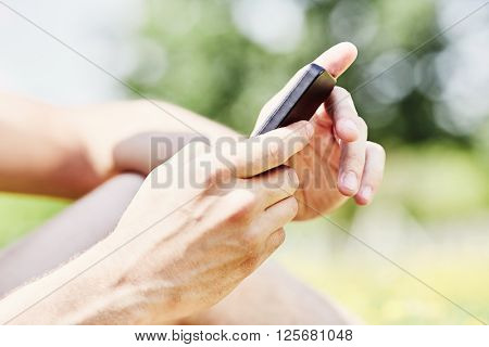 Close up of male hands texting on mobile phone in summer park outdoors - communication concept